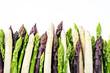 Leinwandbild Motiv roher grüner, weißer und lila Spargel als closeup in einer Reihe mit Textfreiraum oben  – freigestellt