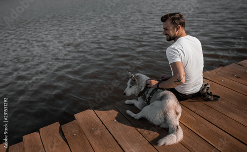 Man with dog sitting on pier