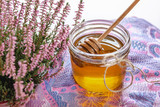 Honey in jar with fresh heather on wooden background