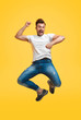 Playful jumping man on yellow background