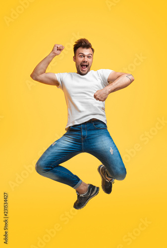 Foto Murales Playful jumping man on yellow background