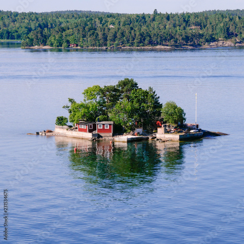 Leinwanddruck Bild Small island in the Stockholm archipelago. Red saunas and cross waves on square frame.