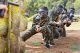 Paintball team running with marker guns - 231539411