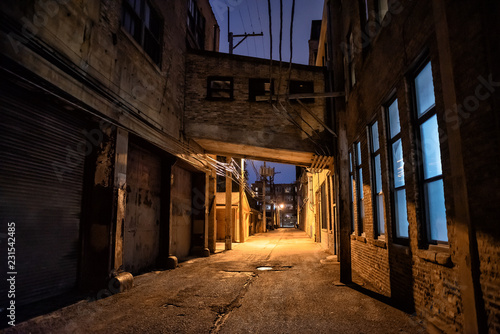 Dark and scary downtown urban city street alley scene with an eerie vintage industrial warehouse factory skyway at night - 231542485
