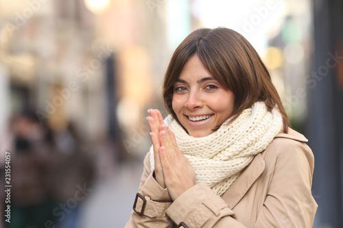 Leinwandbild Motiv Happy woman being cold in the street in winter