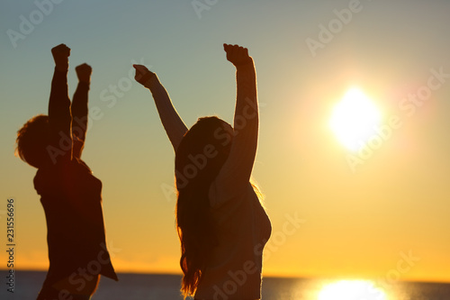 Leinwandbild Motiv Excited friends raising arms at sunset on the beach