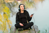 Pretty girl listening music with her headphones in the street - 231557066