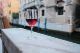 A glass of red wine standing on the parapet of the canal embankment in Venice - 231560639