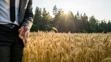 Businessman standing on the left side of an image touching golden ear of wheat - 231564808