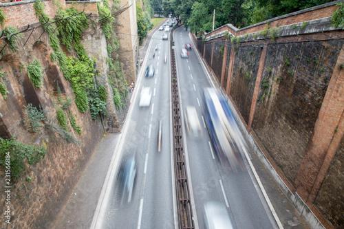 samochody pędzące przez rzymską ścianę