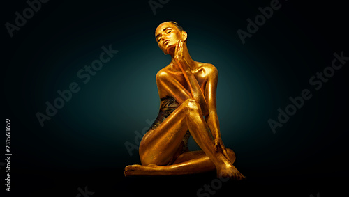 Leinwandbild Motiv High Fashion model girl with bright golden sparkles on her body posing, full length portrait of beautiful sexy woman with glowing body skin. Art design makeup
