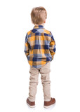 Rear view of little boy with hands in his pockets, isolated on white background - 231583823