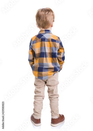 Tylni widok chłopiec z rękami w jego kieszeniach, odosobniony na białym tle