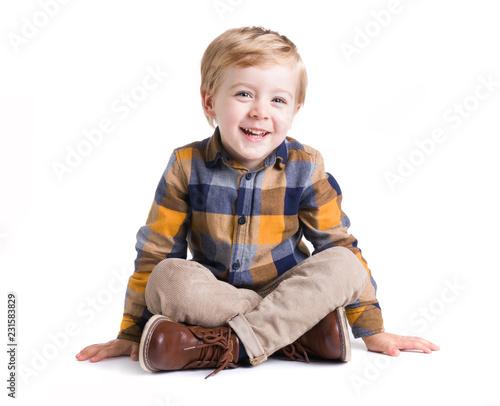 Urocze małe dziecko siedzi na podłodze, odizolowane na białym bacground