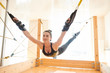 Content satisfied young woman in sports bra and leggings hanging on durable straps joint to wooden planks while she practicing fly yoga in studio