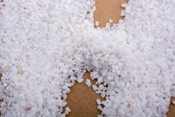 Small white stones scattered on a wooden background