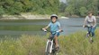 Family on bikes. A child with mother cycling along the river.