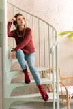 On stairs. Beautiful dark-haired woman wearing dark red sweater sitting on stairs in nice restaurant - 231614841