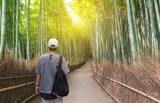 Travel in Japan, a man with backpack travelling at Arashiyama bamboo forest, famous travel destination in Kyoto Japan