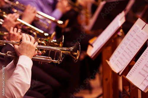 Leinwanddruck Bild Trumpets in the hands of the musicians in the orchestra