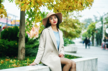 Portrait of a young woman on the streets of the autumn city . A girl in a wide-brimmed felt hat and a light coat