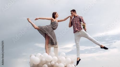 Leinwanddruck Bild High flying romance. Ballet couple into love relations. Romantic relations between ballerina and ballet partner. Couple in love. Ballet dancers falling in love. Reaching the sky