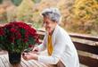 Leinwanddruck Bild - An elderly woman outdoors on a terrace on a sunny day in autumn.