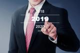 Businessman select 2019 number on digital screen - 231640699