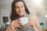 Smiling brunette girl drinking hot tea - 231642896