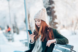Young  woman smiling with smart phone and winter landscape . - 231647810