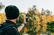 male traveller with backpack holding compass on autumnal background