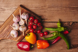 Fresh organic vegetables on wooden board close up. Cherry tomatoes, garlic, peppers and dill on a wooden table..