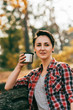 adult woman looking at camera hoding metallic thermos cup on blurred autumnal background