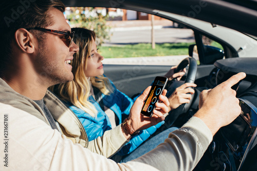 Foto Murales man with smartphone showing direction to wife  in car