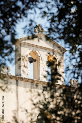 Facciata di chiesa Cattolica con campanile vista attraverso un albero