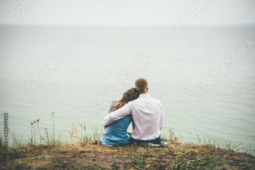 Leinwandbild Motiv Wedding couple is hugging and watching water
