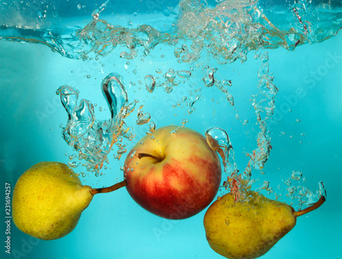Pears and apple splash of water on blue bckground - 231694257