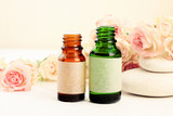 Glass bottles of essential oils on table with delicate beige rose flowers, spa stones. Aromatherapy & wellness - 231697432