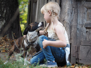 The child gently talks to the dog. Little girl. A dog on a chain