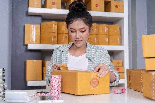 Wall mural woman online entrepreneur using tape to packing parcel box at home office, prepare product for deliver to customer.