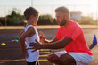Serious young trainer giving lecture to a little boy because of his bad acting on training.
