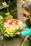 Close-up of a Sad Woman Holding Fowers in front of a Loved one's Gravestone - 231700864