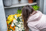 Close-up of a Sad Young Girl Holding Fowers in front of a Loved one's Gravestone - 231702200