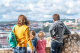 Family of four enjoying city view on a beautiful day. Back view of Father, mother and two children looking at panorama - 231702224