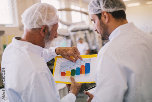 Picture of two male business colleagues in sterile clothes looking at histogram of sales for current month. Standing in bright factory room and talking.