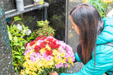 Close-up of a Sad Woman Holding Fowers in front of a Loved one's Gravestone - 231702459