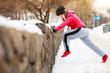 Woman wearing sportswear exercising outside during winter