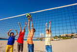 Boys striking volleyball over net on the beach