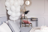 Bunch of white balloons in stylish grey bedroom interior with golden accents, real photo with copy space on the wall - 231706659
