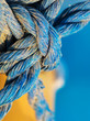 Knot made of blue twisted rope in the grains of sand, extreme close up